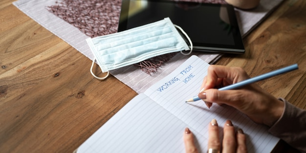Travail à domicile image conceptuelle - femme écrivant dans le bloc-notes avec tablette numérique et masque de protection médicale sur sa table d'accueil.