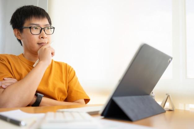 Travail à domicile jeune pigiste ou homme d'affaires travaillant au bureau à domicile avec tablette smartphone.