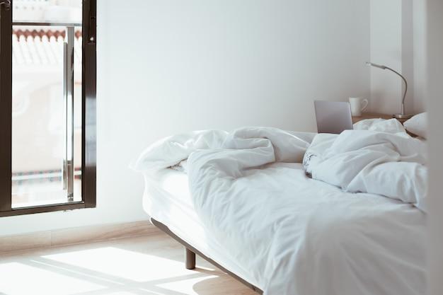 Travail à domicile. ordinateur portable dans un lit défait. bureau à domicile à distance confortable et confortable.