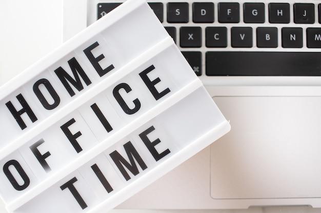 Travail à domicile travail à distance tableau de messages lumineux de médias sociaux inspirant à côté d'un ordinateur portable pour la fermeture de la quarantaine covid-19 de toutes les entreprises.
