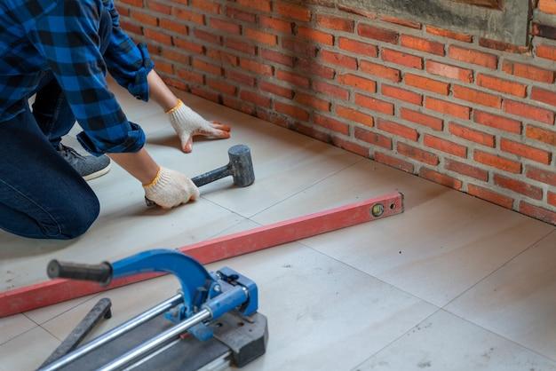 Le travail du carreleur artisanal surveille la qualité du travail, le professionnel vérifie le niveau du bâtiment sur le chantier