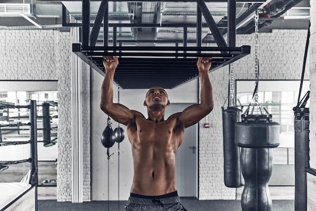 Travail du matin. beau jeune homme africain faisant des tractions tout en faisant de l'exercice dans la salle de sport