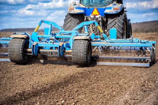 Travail du sol dans le champ avec un tracteur avec une machine traînée.