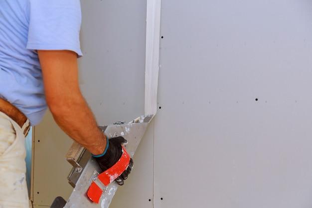 Le travail du travailleur s'aligne sur le mur de la spatule