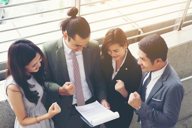 Travail d'équipe d'affaires avec un document entre les mains, regarder du contenu intéressant pendant le déjeuner