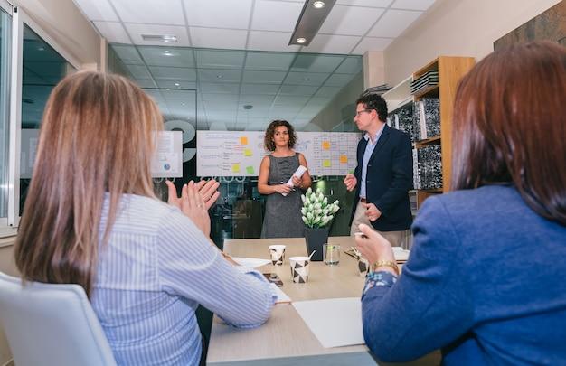 Travail d'équipe applaudissant à une femme chef lors d'une réunion pour célébrer le succès d'un projet d'entreprise au siège