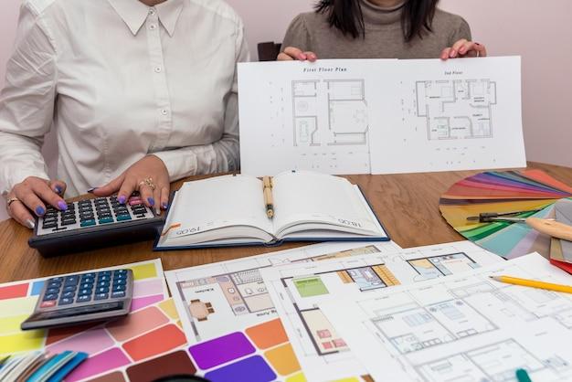 Travail d'équipe de concepteurs au bureau montrant le plan de la maison