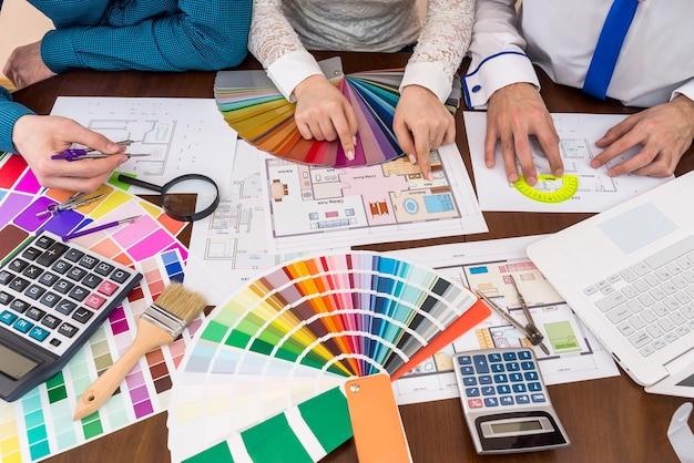 Travail d'équipe des concepteurs choisissant des couleurs pour des salles dans la maison