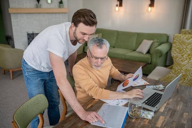 Travail en équipe. deux hommes travaillant ensemble sur un projet et semblant impliqués