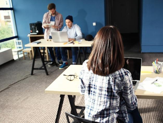 Travail d'équipe discutant. bureau de l'espace ouvert et équipe de démarrage remue-méninges sur un nouveau projet. jeune femme avec dossier papier.