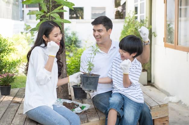 Travail d'équipe du père caucasien, de la mère asiatique et du jeune fils se penchant pour planter un arbre en pot dans la cour avant à la maison, une jeune famille heureuse a du temps libre pendant le week-end.