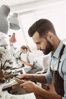 Travail en équipe. l'équipe de bijoutiers travaille ensemble à l'atelier de bijouterie. processus de fabrication de bijoux. équipement de bijouterie. processus de travail.