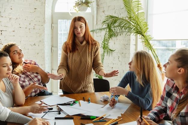 Travail en équipe. des jeunes discutent des droits des femmes et de l'égalité au bureau. des femmes d'affaires ou des employés de bureau de race blanche se sont réunis à propos de problèmes sur le lieu de travail, de pression masculine et de harcèlement.
