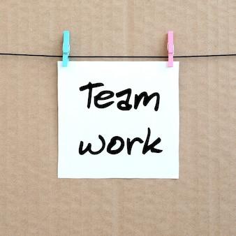 Travail en équipe. la note est écrite sur un autocollant blanc qui pend avec une pince à linge