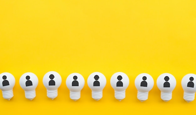 Travail d'équipe à plat avec l'icône humaine sur un groupe d'ampoule sur une couleur pastel