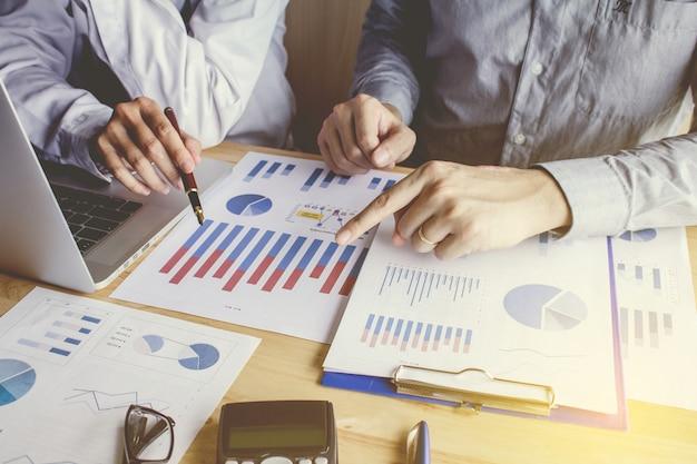 Travail d'équipe point de rencontre pour discuter du graphique de haut en bas de l'économie et de travail sur ordinateur portable.