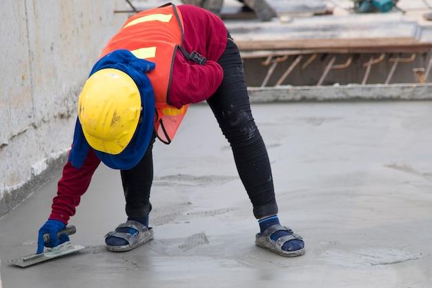 Travail d'équipe de travailleur de la construction en uniforme standard de sécurité coulée de béton