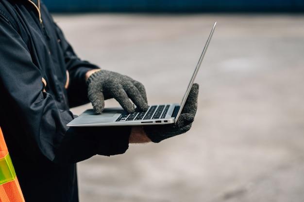 Travail d'équipe des travailleurs homme et femme en tenue de travail de combinaison de sécurité avec casque jaune et utiliser un conteneur de contrôle pour ordinateur portable à l'entrepôt d'expédition de fret.