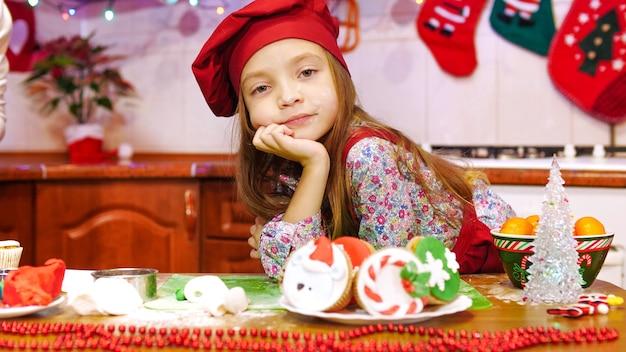 Le travail est terminé et les cupcakes sont prêts. la fille est sale avec de la farine. ambiance d'avant noël.