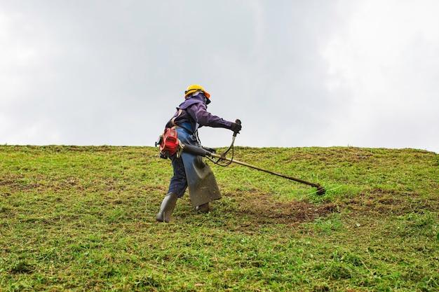 Le travail des femmes porte des vêtements de protection tond sur la colline l'herbe à gazon avec une tondeuse à gazon