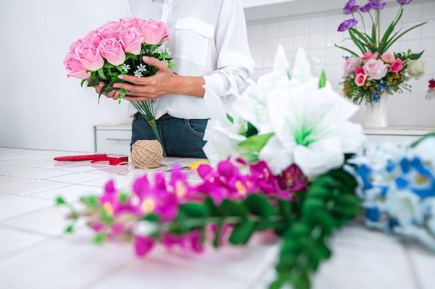 Travail De Fleuriste De Jeune Femme Faisant Organiser Le Concept De Fleur Artificielle De Bricolage, D'artisanat Et De Main. Photo Premium