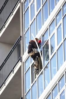 Le travail de grande hauteur met les fenêtres à l'extérieur du nouveau bâtiment