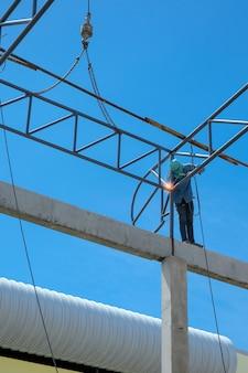 Travail en hauteur, man soudant la structure du toit d'usine dans le chantier de construction.