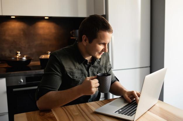 Travail en ligne à domicile. l'homme travaille sur un ordinateur portable à l'intérieur, au bureau dans la cuisine