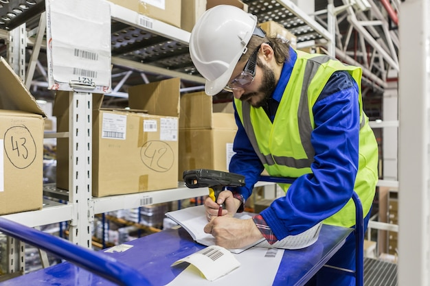 Travail masculin portant une veste jaune uniforme bleue et un casque d'écriture s'appuyant sur une table tenant un lecteur de codes-barres.
