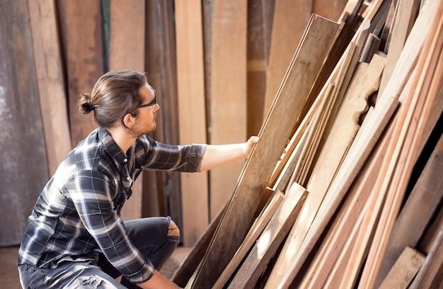 Travail de menuisier dans l'atelier du bois en sélectionnant le bois pour ses woddwork
