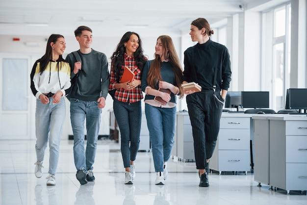 Le travail n'attendra pas. groupe de jeunes marchant dans le bureau à leur pause