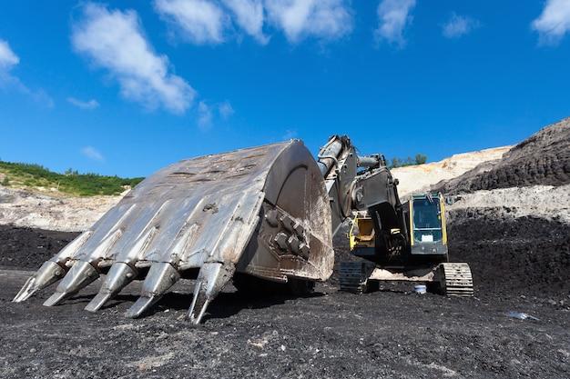 Travail de pelleteuse jaune dans la mine de charbon