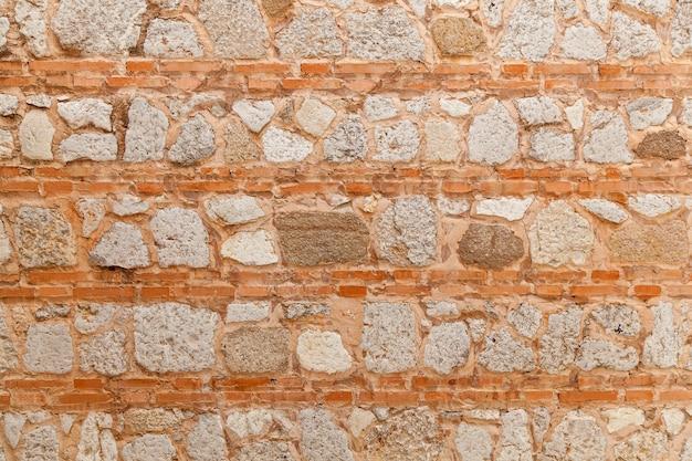 Travail de pierre et de brique antiques dans l'ordre horizontal, partie en pierre du mur