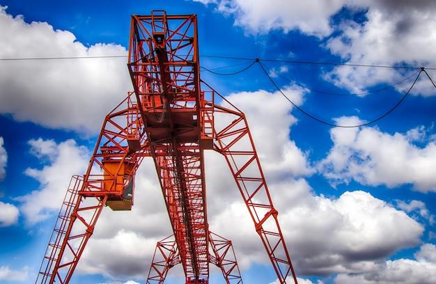 Le travail d'un portique. site industriel. chargement de la cargaison contre un ciel nuageux. photo hdr.