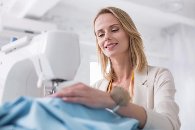 Travail précis. faible angle de tailleur féminin optimiste à l'aide de machine à coudre et souriant