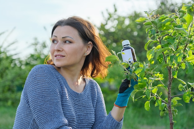 Travail de printemps dans le jardin, bouteille d'engrais chimique, fongicide à la main