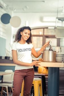 Travail publique. belle femme joyeuse prépare la soupe tout en aidant les gens en tant que bénévole