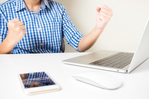 Travail réussi d'hommes d'affaires. de jeunes hommes d'affaires heureux de recevoir de bonnes nouvelles sur les ordinateurs portables.