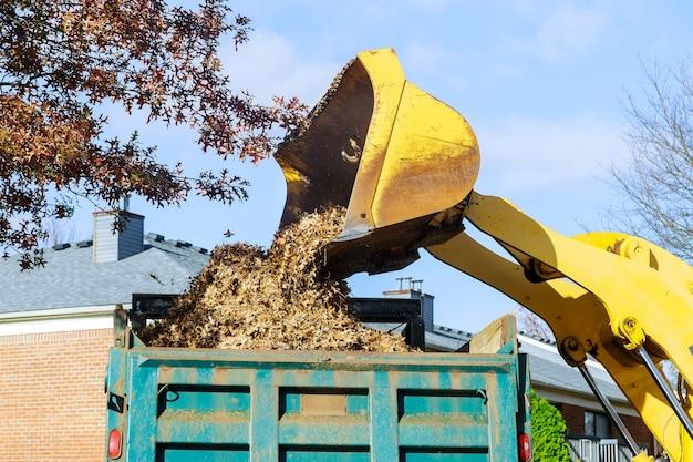 Le travail saisonnier dans l'équipe d'amélioration enlève les feuilles tombées avec une excavatrice un camion améliorant les lieux publics
