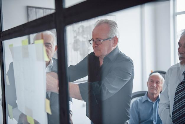Travailler avec des autocollants sur verre. une équipe âgée d'architectes d'affaires âgés a une réunion au bureau.