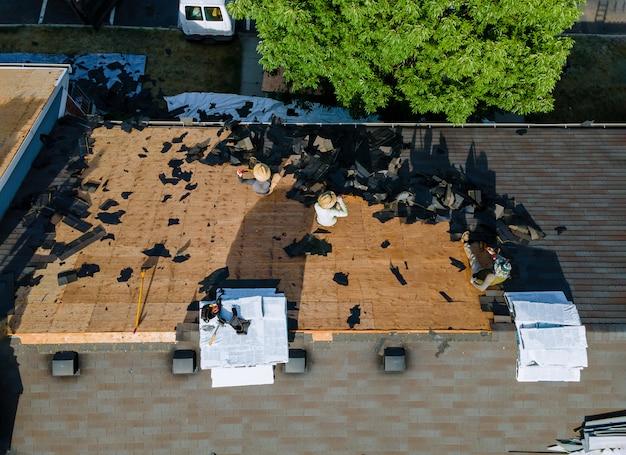 Travailler les couvreurs sur le remplacement du toit d'un immeuble résidentiel