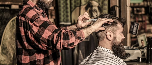 Travailler dans le salon de coiffure. coiffeur homme. coiffeur coupant les cheveux d'un client masculin. homme visitant un coiffeur dans un salon de coiffure.