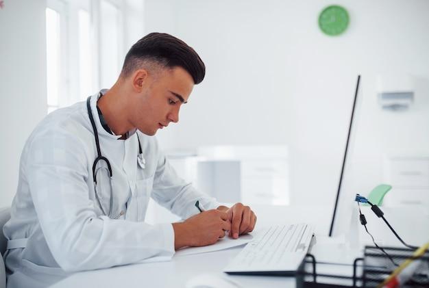 Travailler avec des documents. un jeune médecin de sexe masculin élégant avec stéthoscope est en clinique pendant la journée.