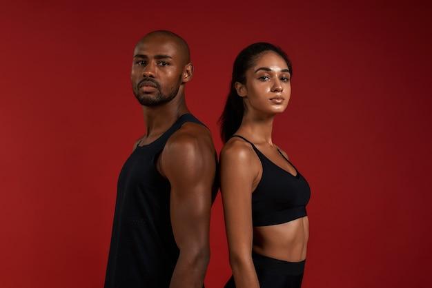 Travailler ensemble un couple de fitness africain jeune et confiant en vêtements de sport regardant la caméra
