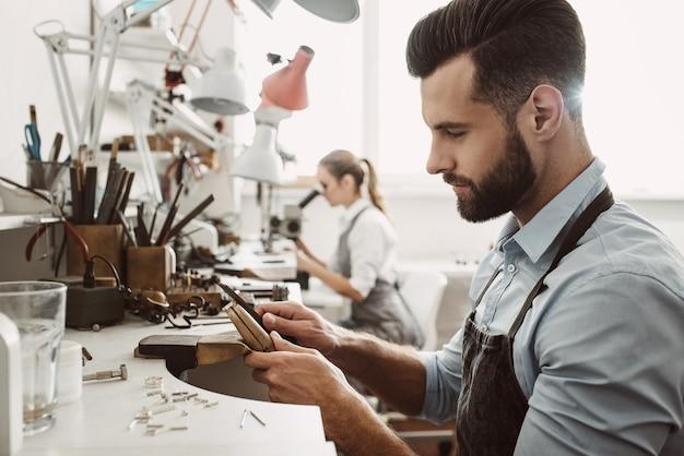 Travailler ensemble. l'équipe de bijoutiers travaille ensemble dans un atelier de fabrication de bijoux. processus de fabrication de bijoux. équipement de bijouterie. processus de travail.