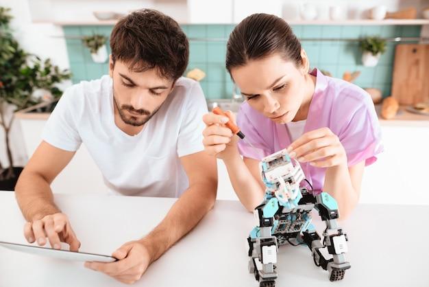 Travailler ensemble. fille aide guy créer robotique.
