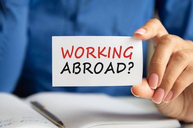 Travailler à l'étranger écrit sur une carte papier à la main de la femme