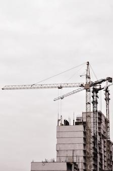 Travailler de hautes grues à l'intérieur pour les grands immeubles en construction contre un ciel bleu clair.