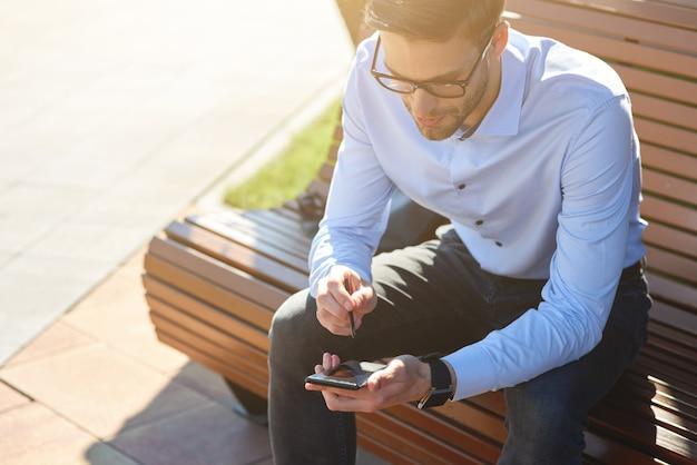 Travailler en ligne à l'extérieur d'un jeune homme d'affaires occupé portant une chemise bleue et des lunettes à l'aide d'un smartphone