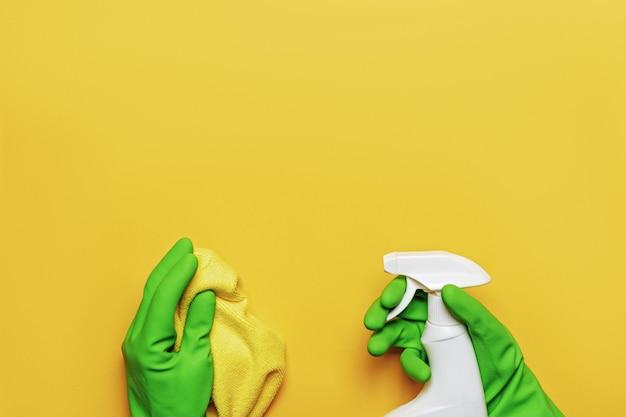 Travailler les mains dans des gants de protection en caoutchouc avec une serviette et un vaporisateur.